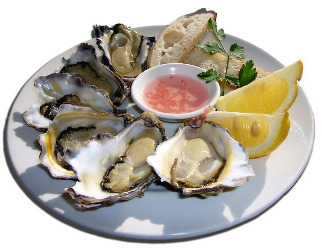 皿上に並べた牡蛎とレモンの画像