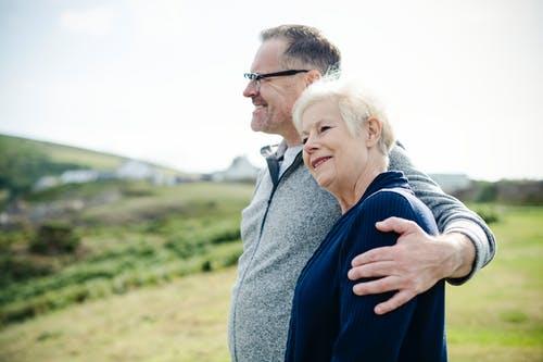 高齢者の男女が山の上で景色を見ている画像