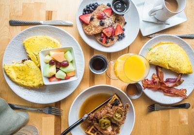 テーブルの上に置かれた多くの種類の朝食の画像