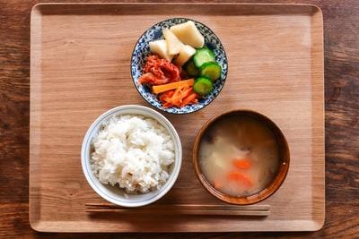 ごはん味噌汁野菜が並べられた食事の画像