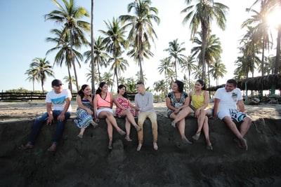 海岸で座って会話する多くの男女の画像