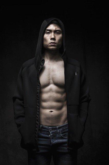 パーカーを被っている腹筋の割れた男性の画像