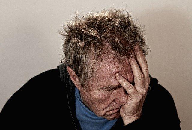 頭を抱え悩んでいる男性の画像