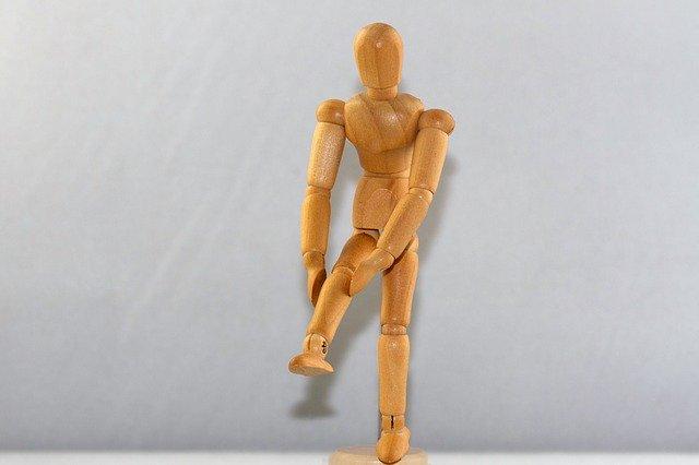 膝を痛そうに押さえている人型の人形の画像
