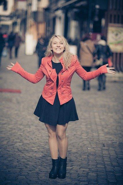 街中で両手を広げている笑顔の赤いコートを着た女性の画像