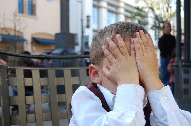 両手で顔を隠す少年の画像