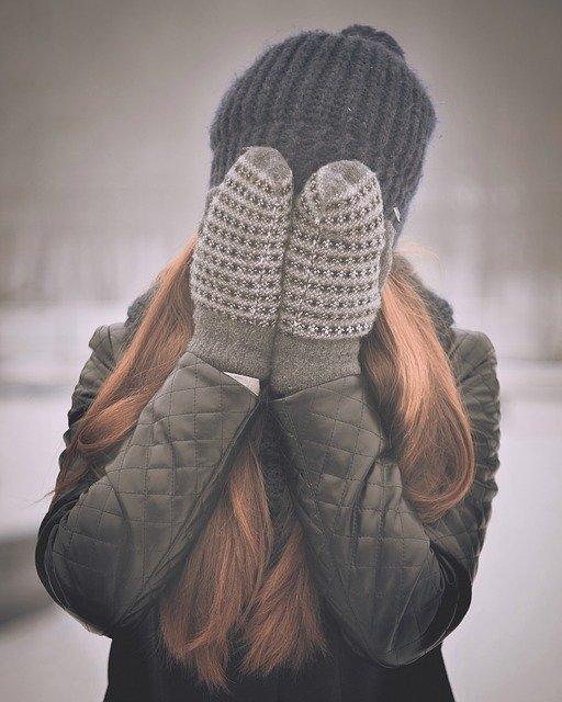 外で厚着をした女性が恥ずかしそうに手で顔を隠している画像