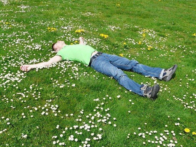 草原で両手を広げ寝そべる男性の画像