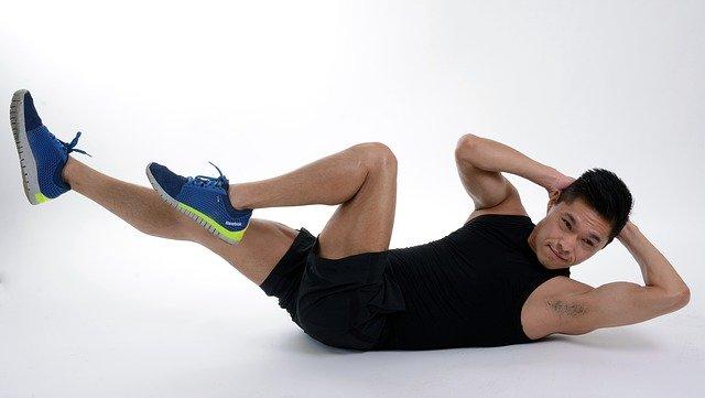 地面で腹筋トレーニングを行う男性の画像