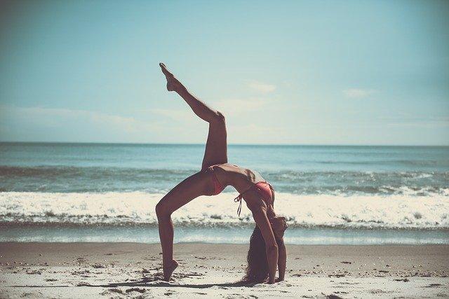 浜辺で水着の女性が片足を挙げてブリッジしている画像