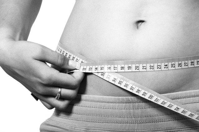 お腹周りをメジャーで測る人の画像