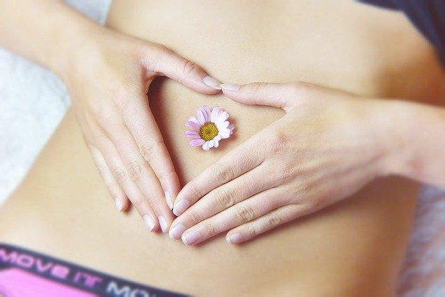 女性がお腹の上に手でハートを作りその中に1輪の花をお腹の上に置いている画像
