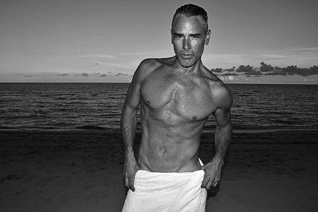 浜辺で上半身裸の腰にタオルを巻いている男性の画像