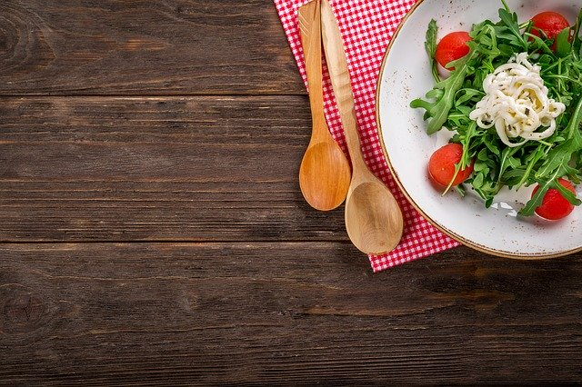 テーブルの上にサラダと木のスプーンがある画像