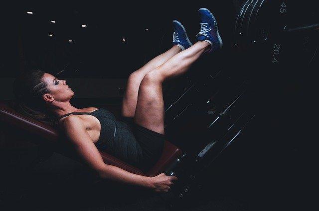 ジム内でマシンで脚をトレーニングしている女性の画像