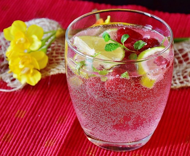 テーブルの上にグラスに入ったレモンと炭酸水の画像