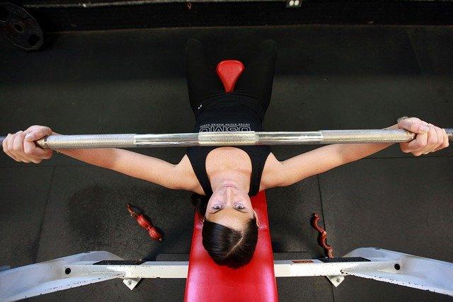 ジムでバーベルトレーニングを行う女性の画像