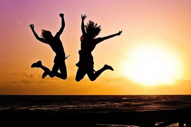 浜辺でジャンプしている2人の画像