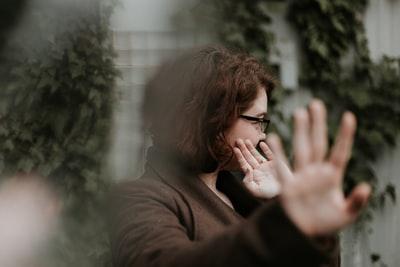 外でこちらに手を向けて拒絶している女性の画像