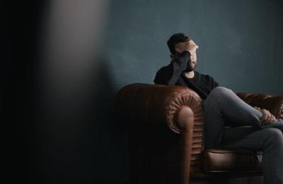 椅子に座り頭を抱えている男性の画像