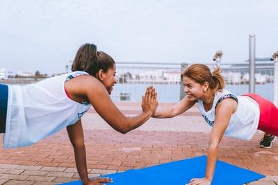 女性2人が手と手をタッチしながら運動している画像