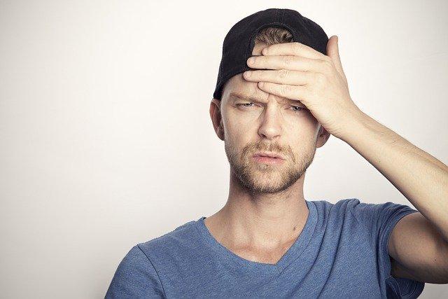 頭を抱えて悩んでいる男性の画像