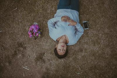 外で横になって寝ている女性の画像