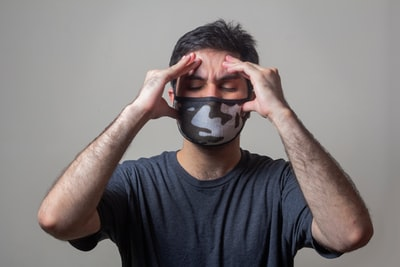 マスクをして頭を押さえている男性の画像